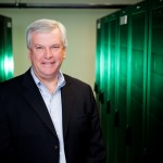 corporate headshot of a guy in a server room with a green background