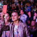 fan girl at concert event taking photography with her cell phone