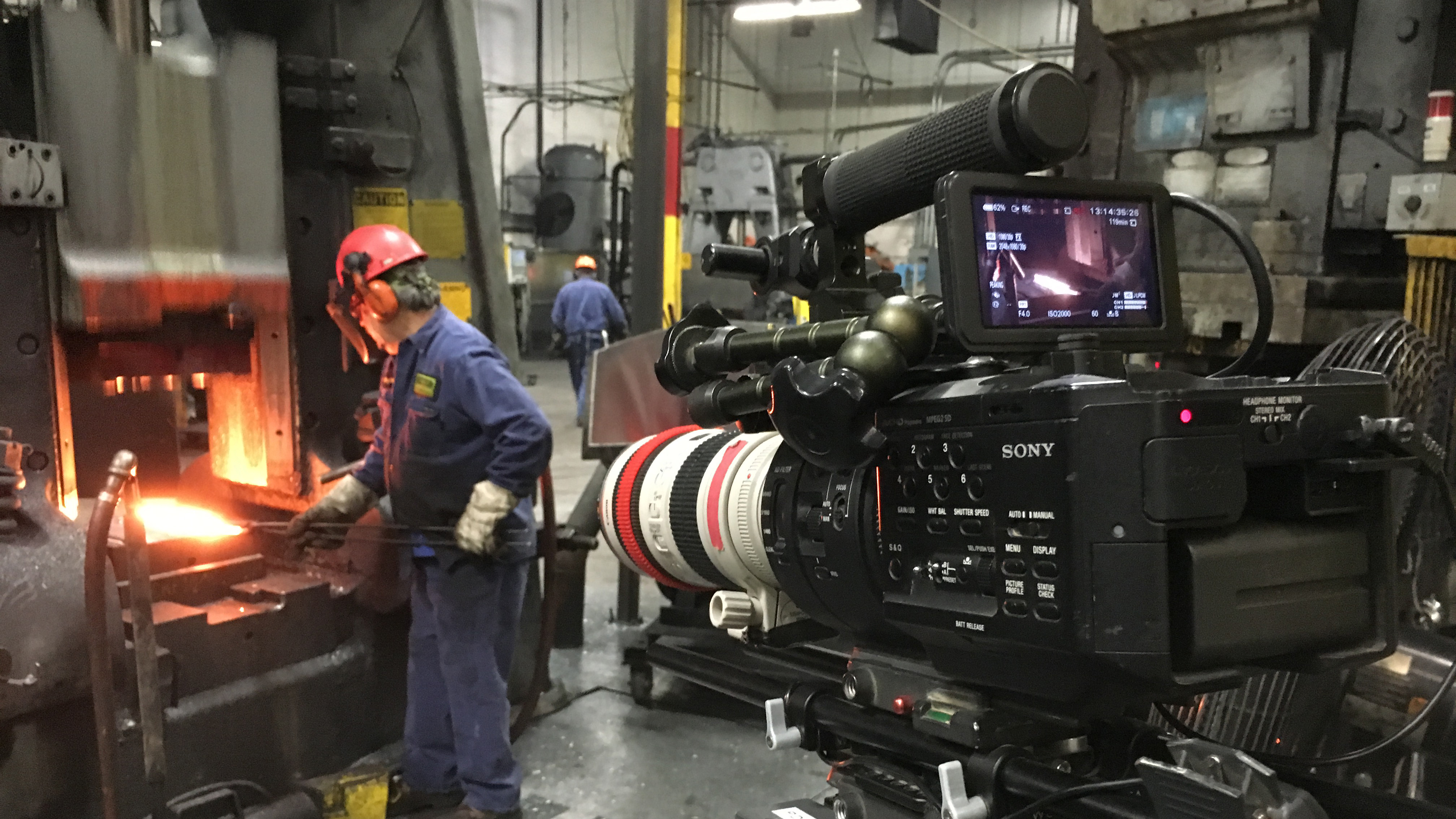 a professional video camera capturing someone working in a kiln