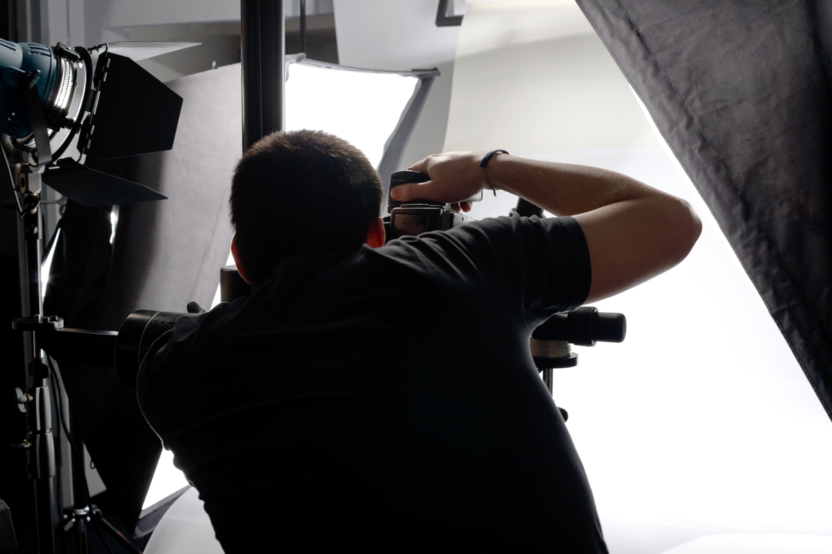 View from behind of photographer at work in his studio. He has a camera mounted on a tripod and is seen looking through the viewfinder. Various lights are also seen to his left and right.